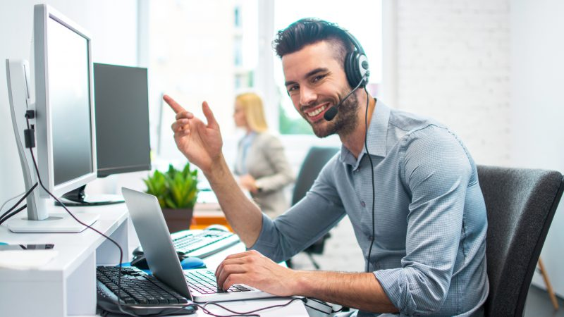 Attractive businessman with headset using laptop and computer in office